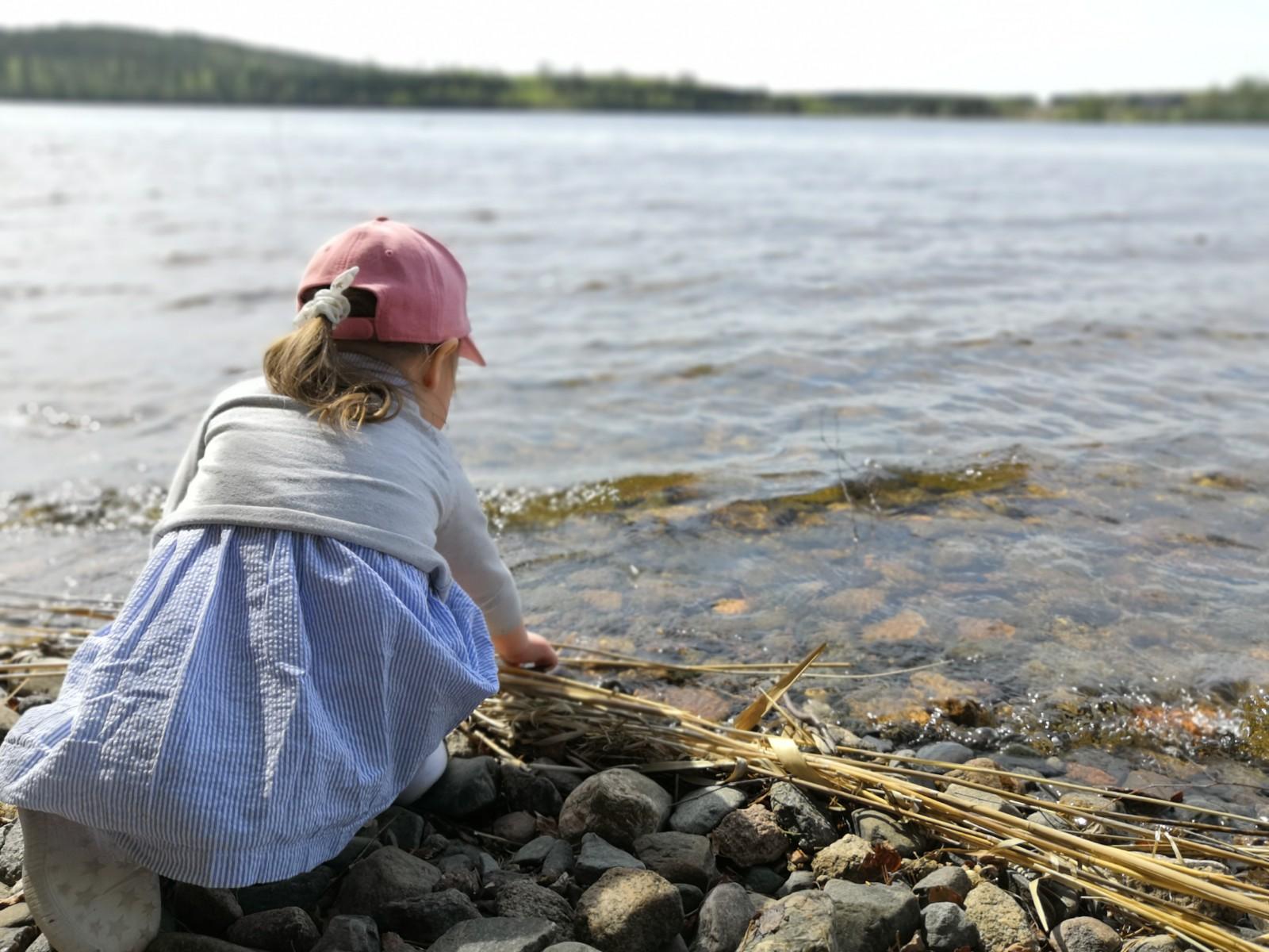 Lapsi kerää rantakiviä Keitelejärven rannalla.