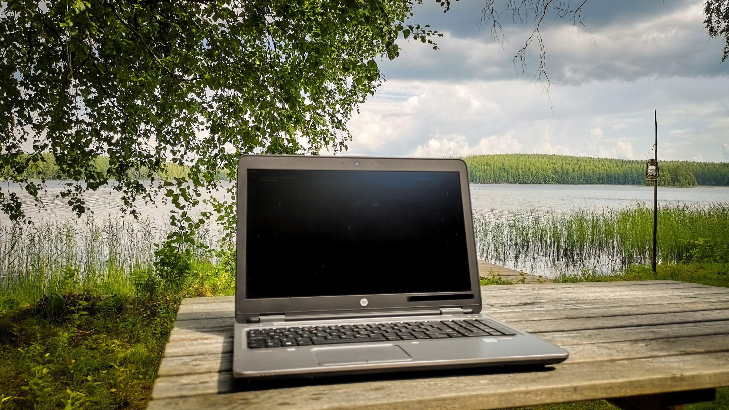 tietokone pöydällä järvimaisemassa